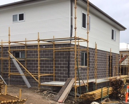A two-storey building in the final stages of construction. Scaffolding being removed, upper corrugated iron and lower storey brick walls complete.