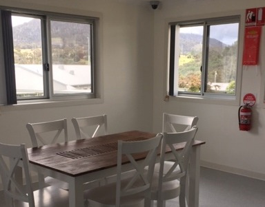 Wooden dining table with six white chairs in dining space with views to mourntains.  Fire safety equipment on wall.