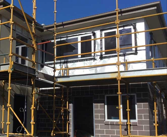 Two-storey building in progress. Scaffold on exterior.  Lower level wall completed, upper level insulation being installed prior to fitting of outer wall.