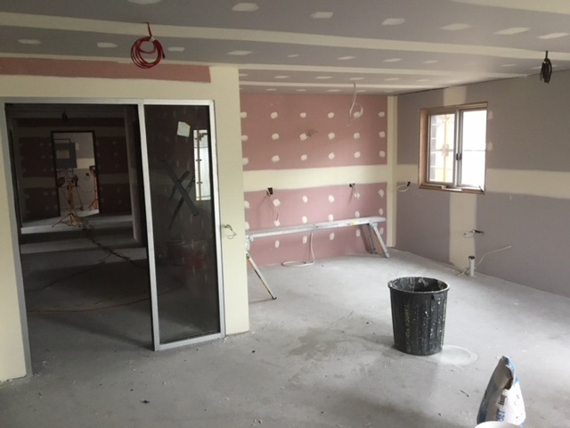 Room under construction with plasterboard in progress with window and glass interior door in place.
