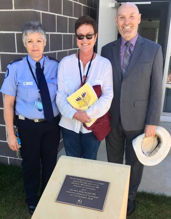 Left to right: Lady in uniform , smiling lady in casual clothes wearing sunglasses, smiling gentleman in jacket and tie clutching sunhat, next to a metal plaque in a sandstone plinth.