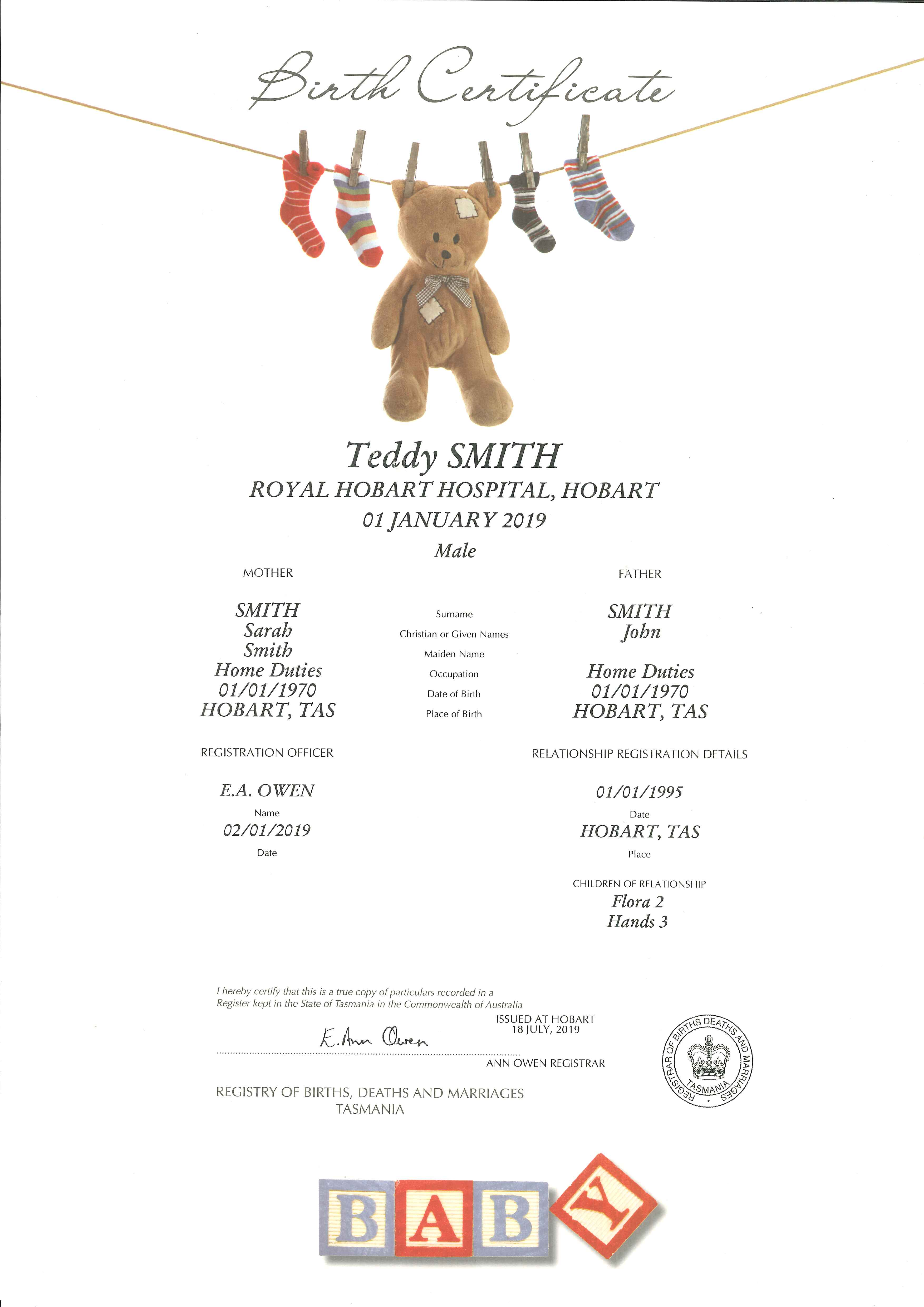 Decorative Birth Certificate. At the top of the page is a washing line with a teddy bear and baby's socks pegged on the single line. The teddy is brown with patches and the socks are multi coloured stripes, mainly in reds and blue. At the bottom of the page are baby blocks in shades of red and blue (matching the socks) spelling BABY.