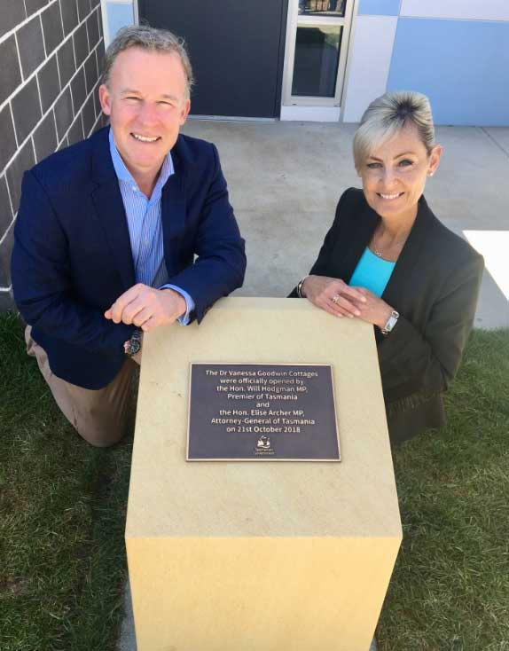 Gentleman on left with lady on right in smart casual attire, next to a metal plaque in a sandstone plinth.