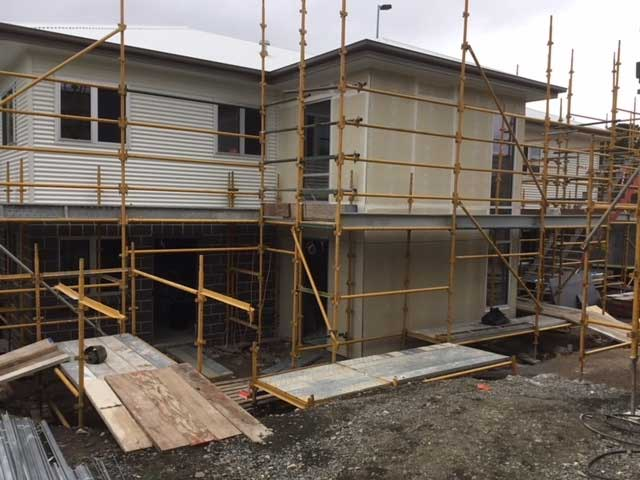 Partially completed two-storey accommodation building.  Scaffolding in place. Windows in place and exterior wall casing ready for painting.