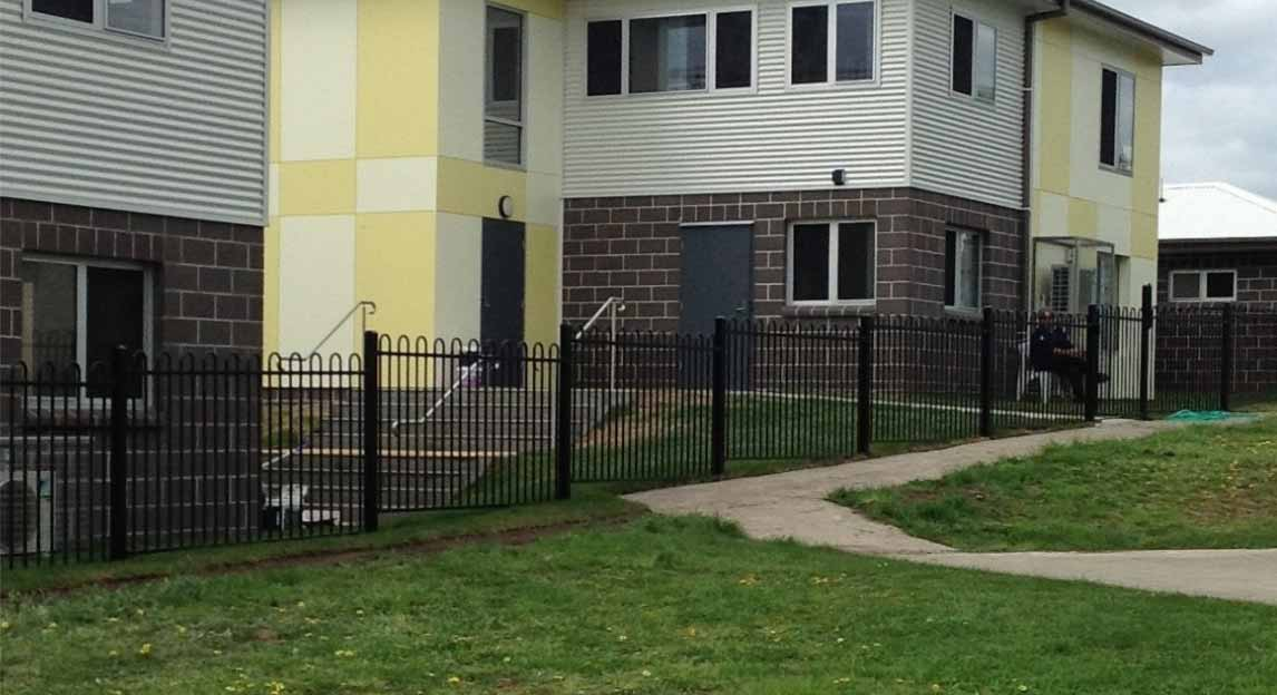 A group of two-storey buildings behind a perimeter fence.  Grass and footpath in front of fence.
