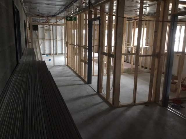 Internal view of accommodation building in early internal construction stage, showing the stud framework for the internal walls and doorways.  Windows in place.