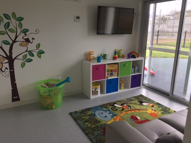 Indoor play area with brightly coloured toys and play mat.  There is a playful tree decal on the wall.