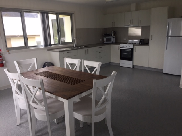 Open plan kitchen dining area.  Wooden-topped table with white legs and matching white chairs.  L-shaped kitchen arrangement including benches, cupboards, microwave, stove and fridge.