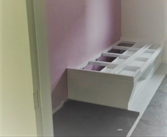 Single bed base being constructed in small room with grey floor and pink wall.