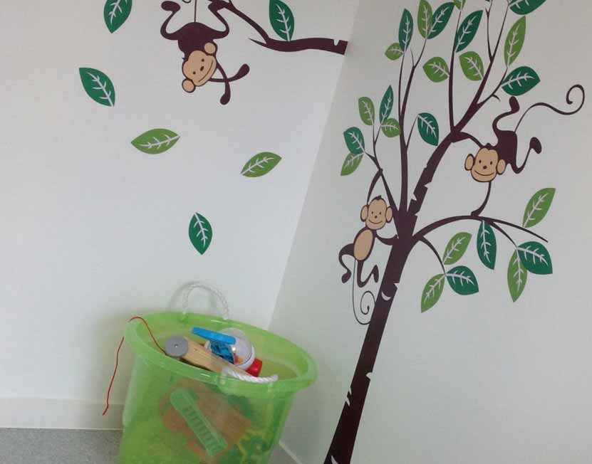 Bucket of toys in front of playful tree wall decal.