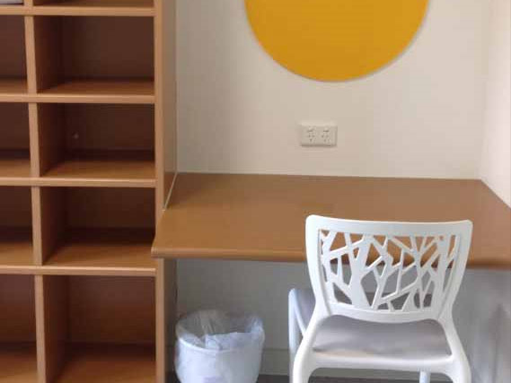 Wooden shelving and desk unit with white study chair, small tv and bright yellow felt pinboard.