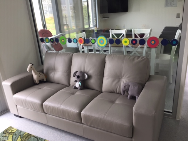View over couch with soft toys on it through glass to dining area with chairs, baby high chair, table and tv.