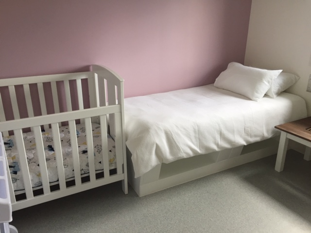 Single bed with cot at foot against a pink wall.